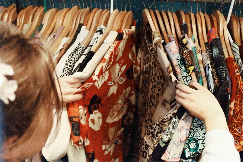 Hvorfor velge skyvedørsgarderobe, Bilde: dame som blar i kjoler som henger på kleshengere